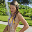 Stok fotoğraf: Teen age girl taking shower outdoors
