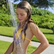 Foto Stock: Teen age girl taking shower outdoors