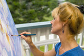 Female artist painting on canvas — Stock Photo