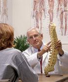 Chiropraktiker in seinem büro mit patienten — Stockfoto