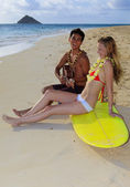 Beachboy plays his ukulele for girl — Stok fotoğraf