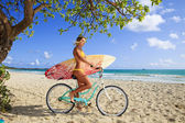 Girl on her bicycle with surfboard — Stok fotoğraf