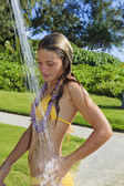 Niña de edad adolescente tomando una ducha al aire libre — Foto de Stock