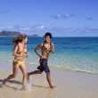 Young couple running on the beach — Stock Photo #2862373