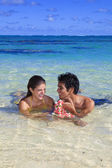 Couple frolic in the tropical water — Stock Photo