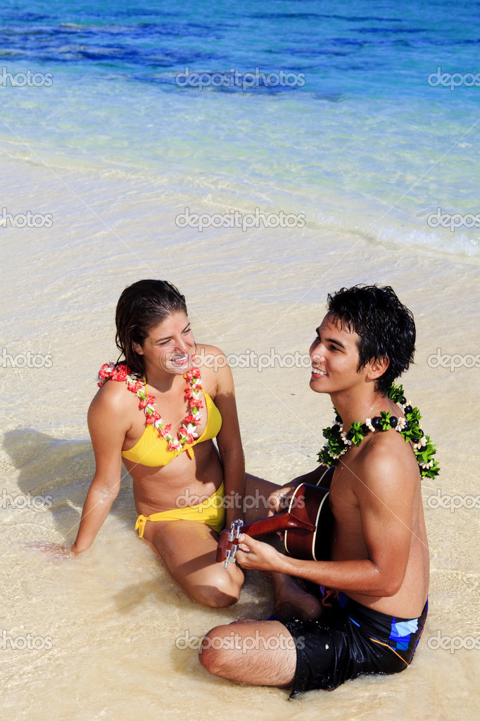 Pacific island man plays his ukulele for a young woman on a hawaii beach — Stock Photo #2862659