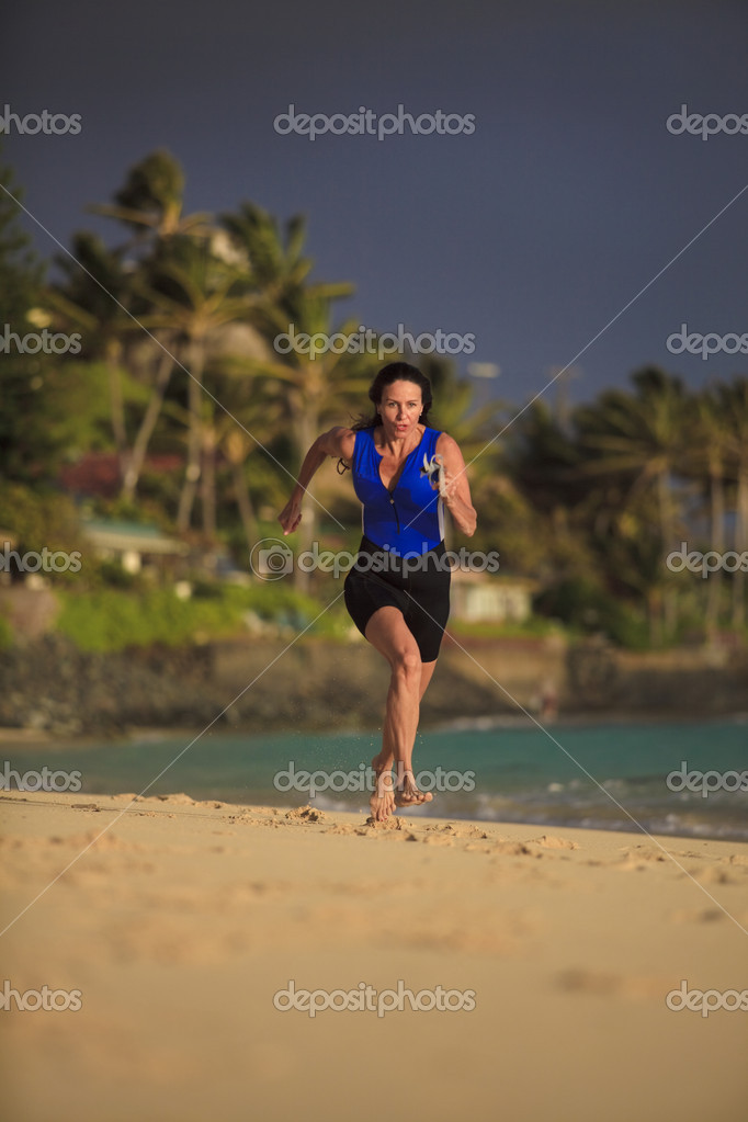 Female triathlete running at the beach at sunrise in hawaii — Stock Photo #3028332