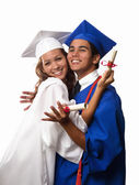 College graduates in cap and gown — Stockfoto