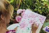 Artist painting flowers — Stock Photo