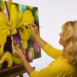 Foto Stock: Female artist painting dendrobium orchids