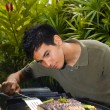Young Asian American man grilling lamb chops - Стоковая фотография