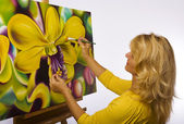 Female artist painting dendrobium orchids — Stock Photo