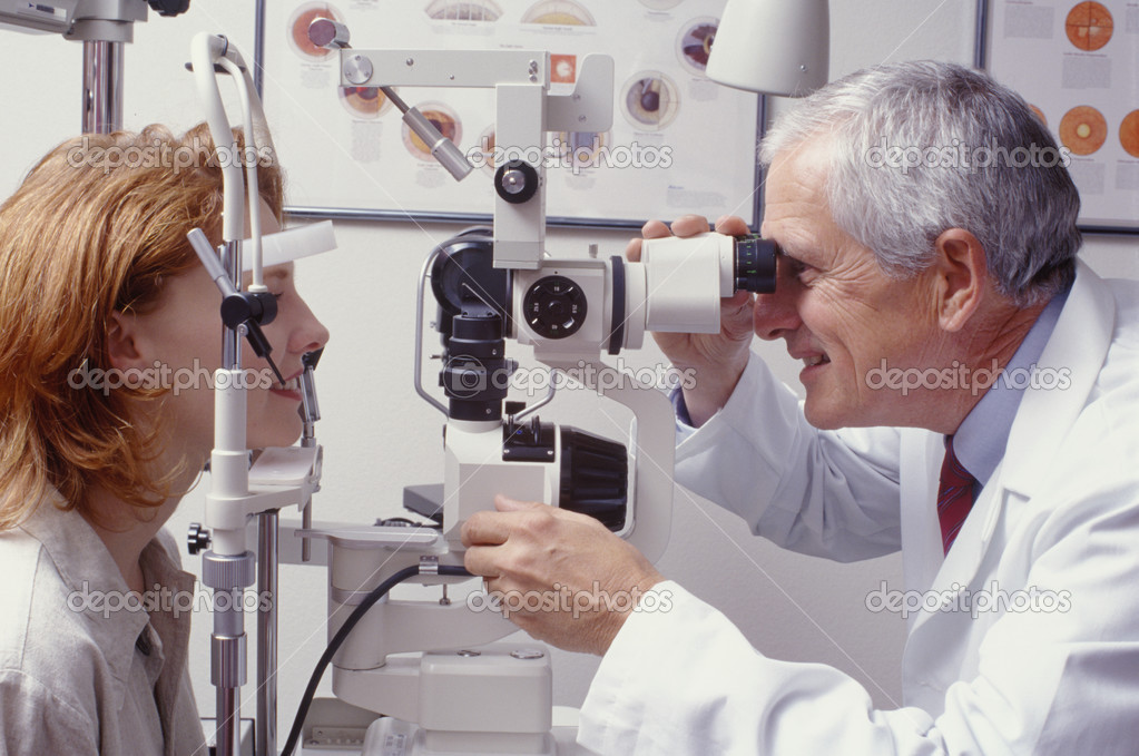 Optometrist with patient, giving an eye examination — Stock Photo #3409024