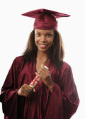 Female college graduate in cap and gown — ストック写真