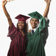 Multi racial couple in cap and gown — Stock Photo