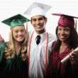 Three graduates in cap and gown - Stock Photo