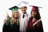 Tři absolventi v čepici a šaty — Stock fotografie