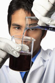 Lab technician with beaker and flask — Stock Photo