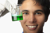 Lab technician holding a beaker — Stock Photo