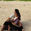 Young mixed race couple sitting on the sand — Стоковая фотография