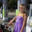 Beautiful teenage girl putting gas into her car — Stock Photo