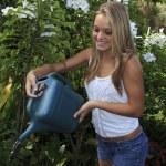 Beautiful teenage girl watering her garden — Stock Photo #3568023