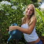 Beautiful teenage girl watering her garden — Stock Photo