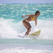 Girl in a yellow bikini surfing — Stock Photo #3698342