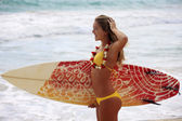Blond girl in a yellow bikini with her surfboard — Stock Photo