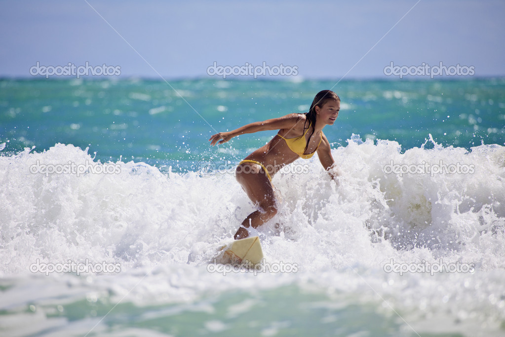 Teenage girl in a yellow bikini surfing in Hawaii — Stock Photo #3698340