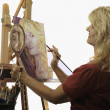 Rtist in her fifties painting a self portrait - Stock Photo