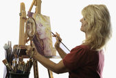 Rtist in her fifties painting a self portrait — Stock Photo