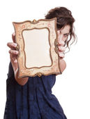 Woman holding an picture frame — Stockfoto