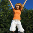 Foto Stock: Girl Jumping on Trampoline