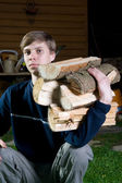 The young sitting guy with fire wood — Stock Photo