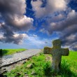 Stone cross on the neglected grave — Stock Photo