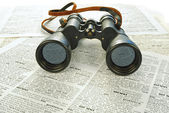 Black binoculars and news — Stock Photo