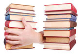 Pile of old books and hand — Stock Photo