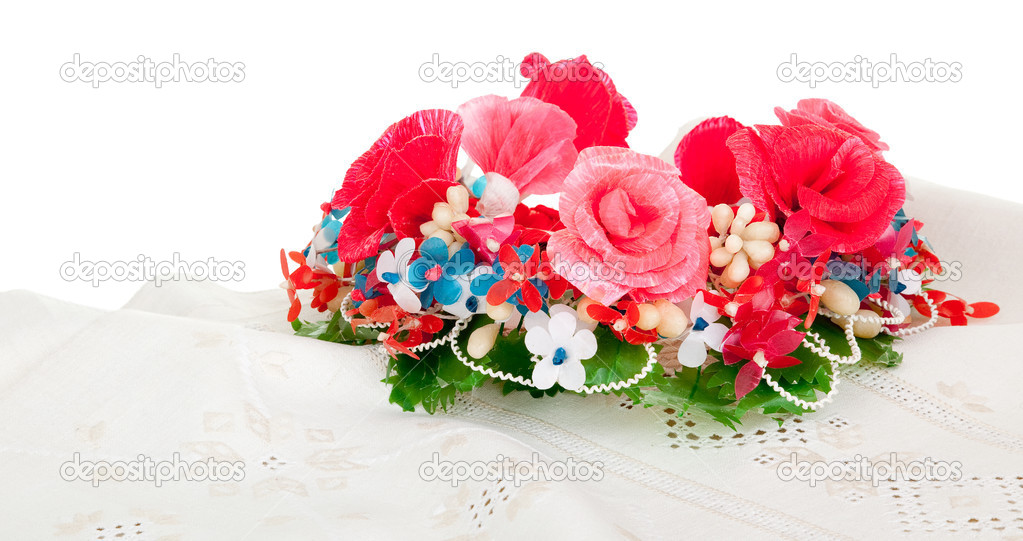 Old Ukrainian embroidery on the simple canvas and a wreath of artificial flowers — Stock Photo #2863024