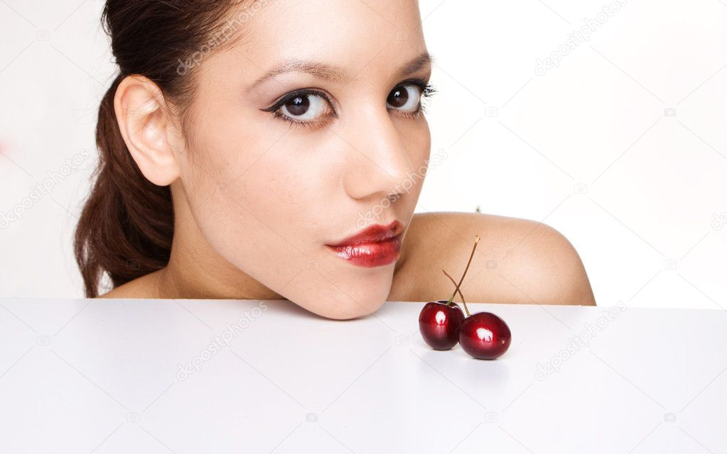 Portrait of woman on white holding red cherries on her lips — Стоковая фотография #2980040