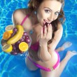 Woman eating fruit in pool — Stock Photo