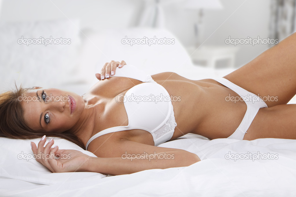 Studio portrait of young beautiful woman on bed — Stock Photo #3224934