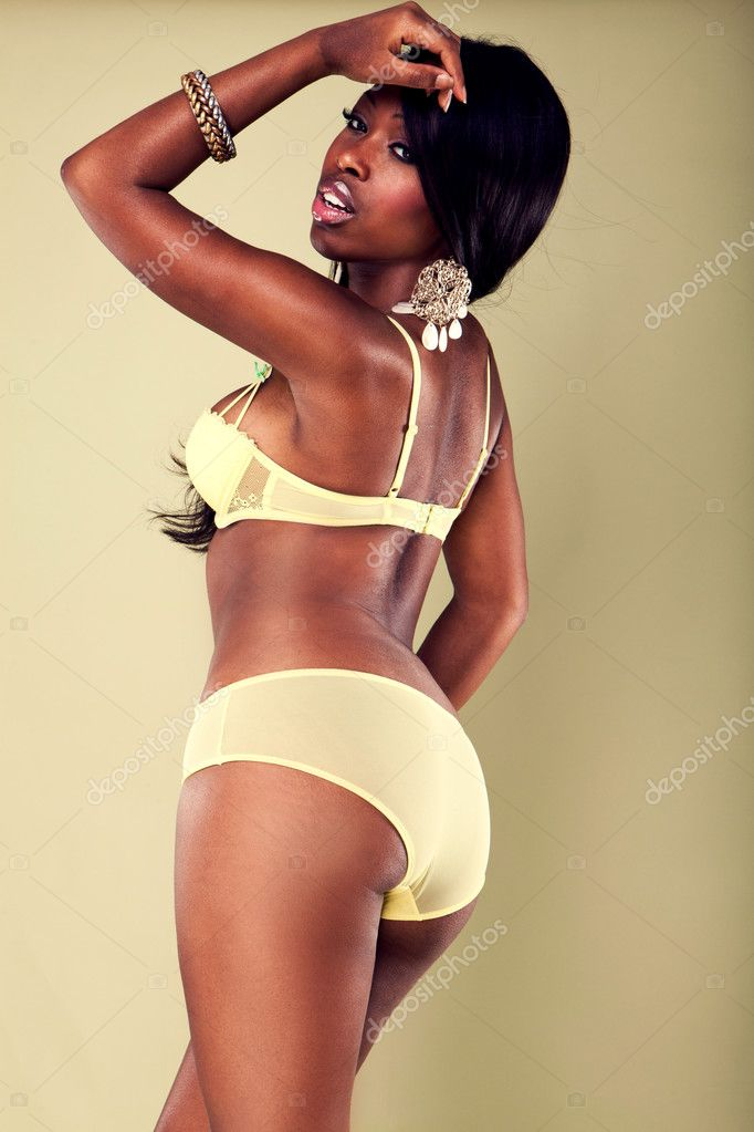 Sexy African American young woman wearing erotic yellow lingerie — Stock Photo #3697021
