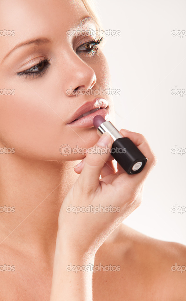 Attractive young woman using lipgloss in the bathroom at home — Stock Photo #3746576