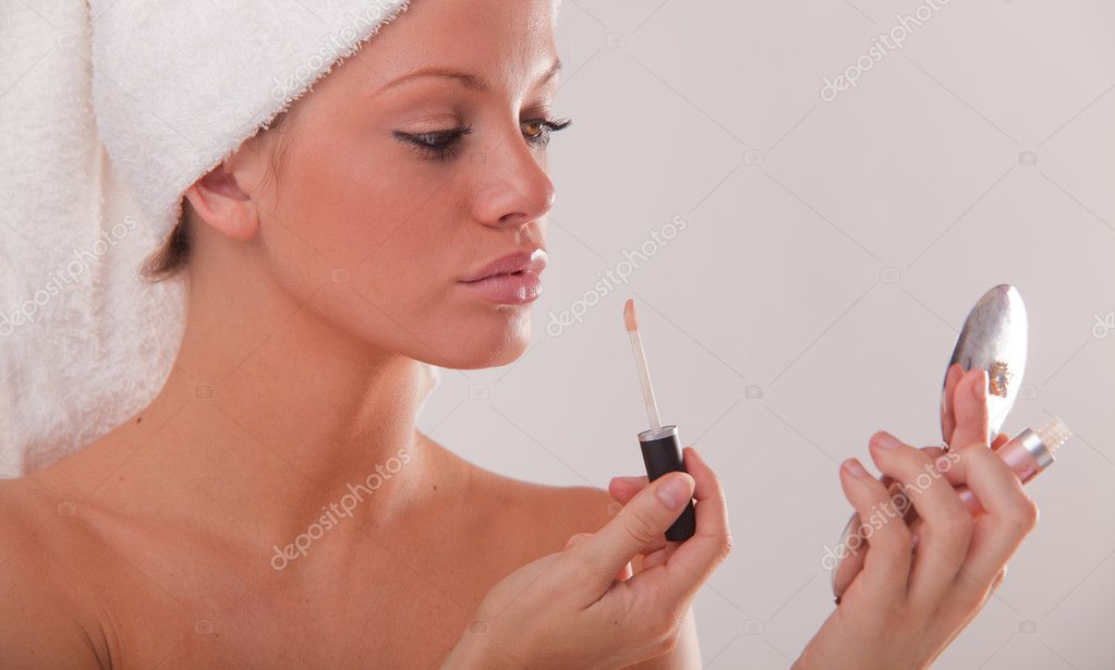 Attractive young woman using lipgloss in the bathroom at home — Stock Photo #3746599