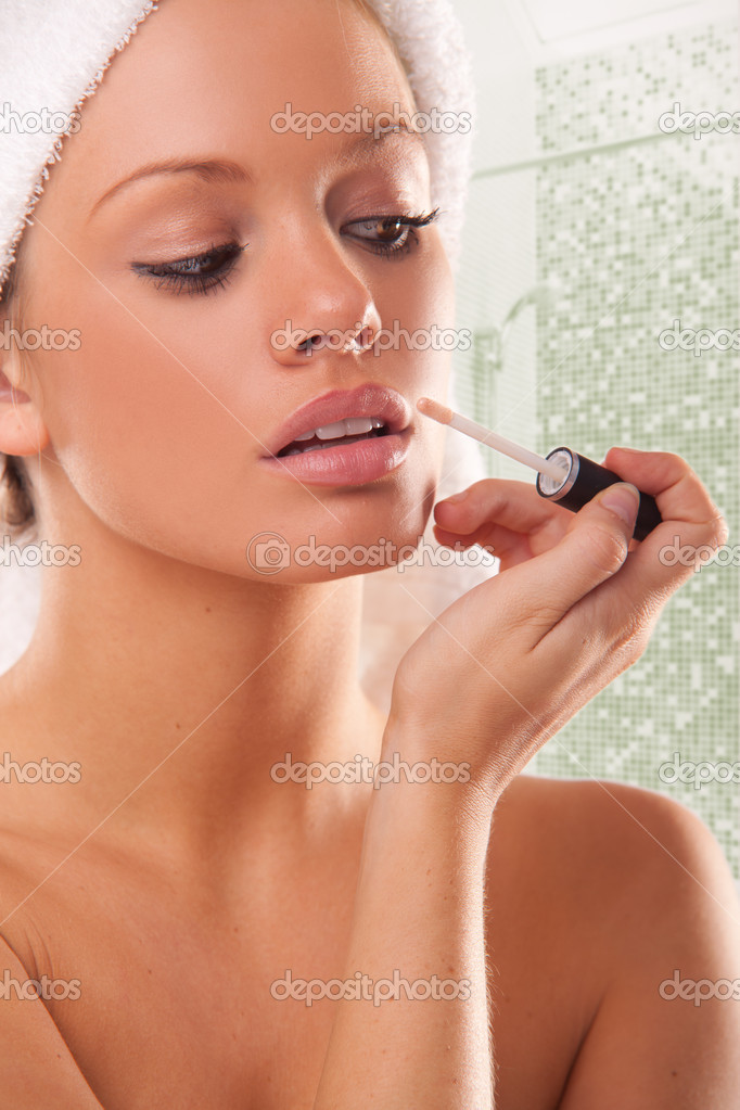 Attractive young woman using lipgloss in the bathroom at home — Stock Photo #3746622