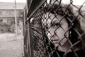 Das mädchen hinter einem zaun — Stockfoto