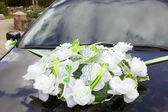 Colorful flowers on grey car — Stock Photo
