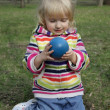 The little girl is considering a ball — Stockfoto