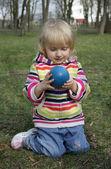 Küçük kız, bir top göz önünde bulundurarak — Stok fotoğraf